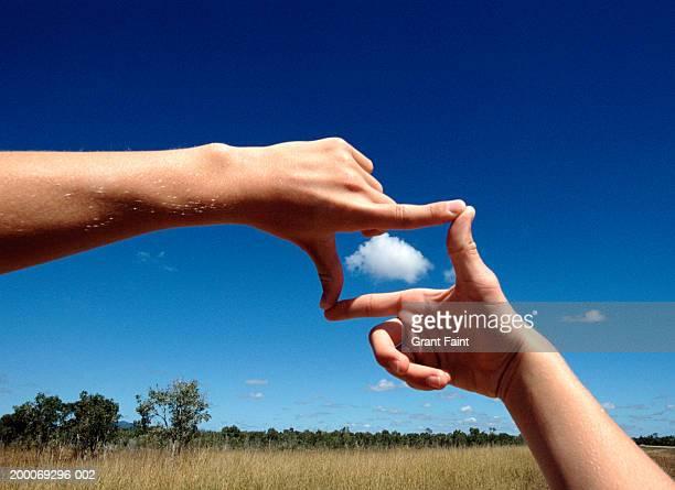 Man framing cloud, close-up of hands