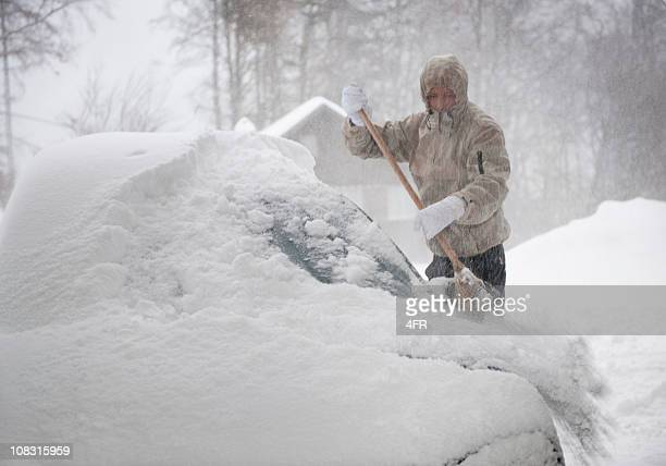 Man freeing car from snow in a blizzard (XXXL)