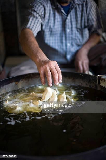 A man fries samosas at the Old and Famous Jalebi Wala Delhi India