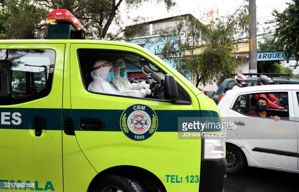 A man from a taxi looks at municipal firefighters after they transferred a patient allegedly infected with the novel coronavirus at the COVID19 unit...
