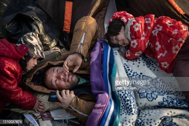 A man from Afghanistan rests as children play around him at a small refugee camp on the Turkish shoreline of the Evros River on March 03 2020 in...