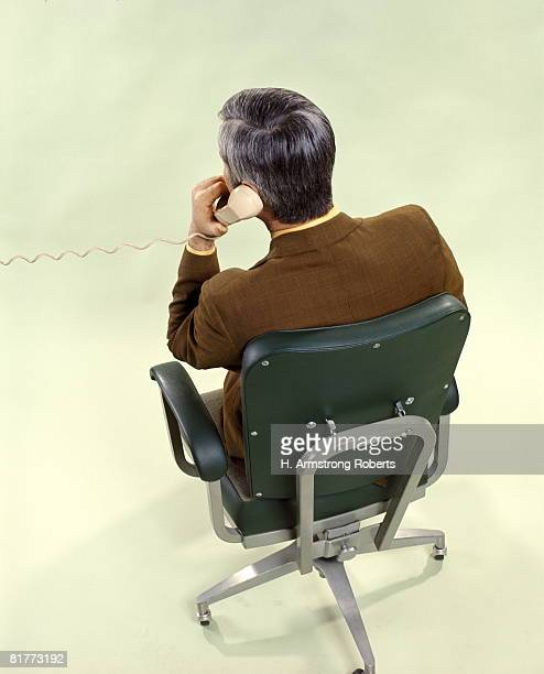 Man From Back Sitting Office Chair Talking On Telephone Phone Business Businessman Salesman Men.