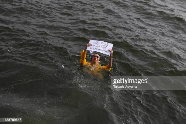 A man from Hong Kong jump in the Sea during a protest on June 28 2019 in Osaka Japan US President Donald Trump arrived in Osaka on Thursday for the...