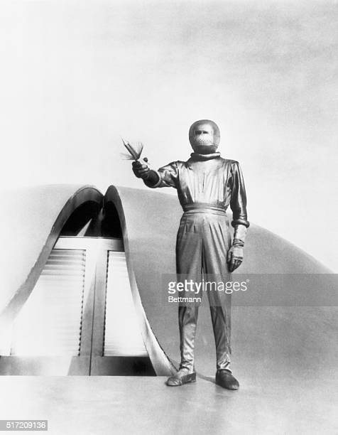 """Man from outerspace stands on the roof of his UFO. Scene from the 1951 movie, """"The Dday the Earth Stood Still."""""""