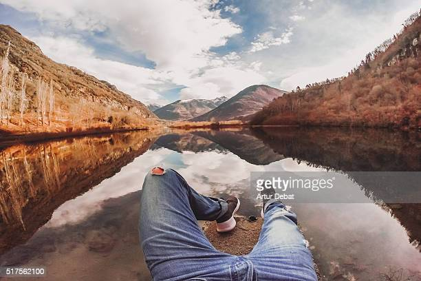 Man from personal point of view contemplating the beautiful water reflection on the lake from the dock with stunning mountain landscape in the Catalan Pyrenees.