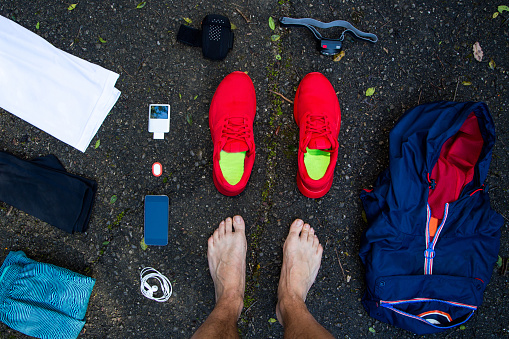 Man from personal point of view knolling all his running stuff for a race in a wet  dark asphalt in outdoors with nice composition and vivid colors. - gettyimageskorea