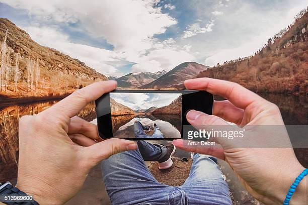 Man from personal point of view taking pictures with smartphone of the beautiful lake with the Pyrenees mountains in the Catalonia region.