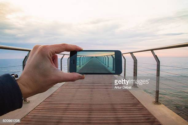 Man from personal point of view taking pictures with smartphone playing with perspective of a straight pedestrian dock over the sea on sunrise.