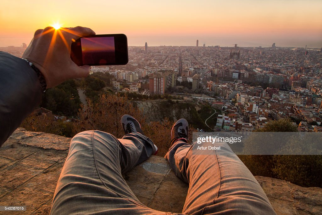 Man from pov taking pictures on Barcelona sunrise. : Stock Photo