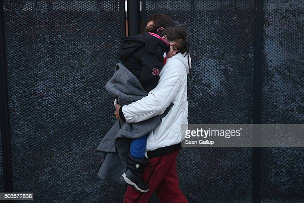 A man from Syria carries his sleeping daughter as he walks to a police van after Danish police found them and other migrants while checking the...