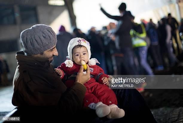 A man from Syria feeds his daughter as asylum seekers line up in front of the State Office of Health and Social Affairs registration centre in Berlin...