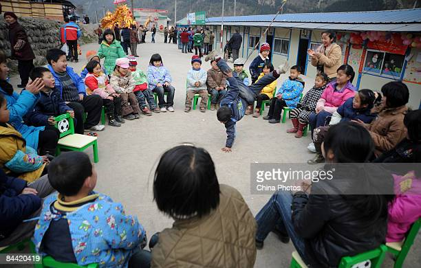 Man from the earthquake hit Province of Sichuan play games with volunteers at the Hongbai Township on January 23, 2009 in Shifang of Sichuan...