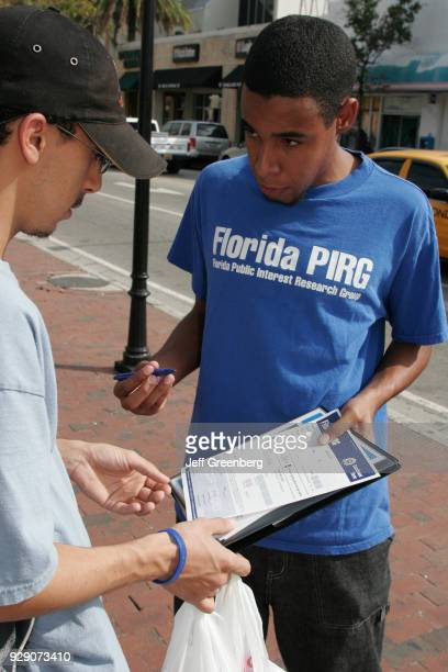A man from the public interest research group asking a man to sign a petition
