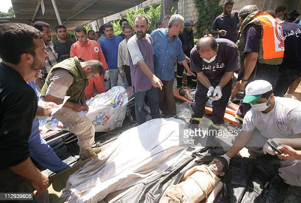 A man from the village of Qana helps Lebanese medical workers identify the bodies delivered to a hospital in the port city of Tyre Sunday July 30...