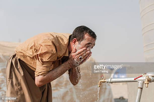 A man from the village of Tob Zawa which was recently taken from ISIS washes his face at a water tapstand in a recently opened camp for people who...