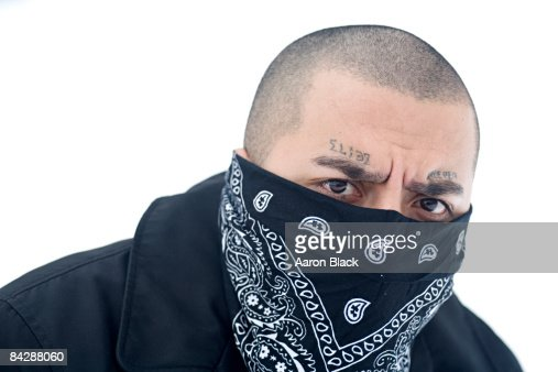 man frowning with a bandana covering his face stock photo