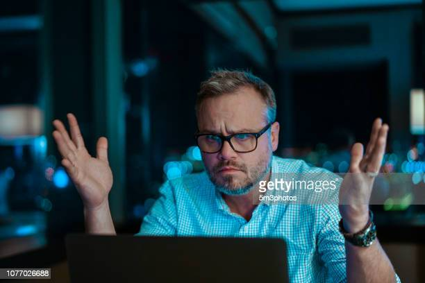 man frustrated upset hacked using online computer for work or banking personal finances and identity theft - identity theft stock pictures, royalty-free photos & images