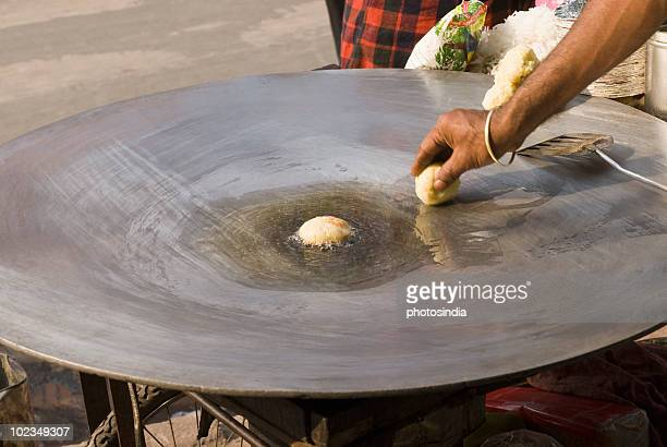 Man frying aloo tikki on a griddle, Delhi, India