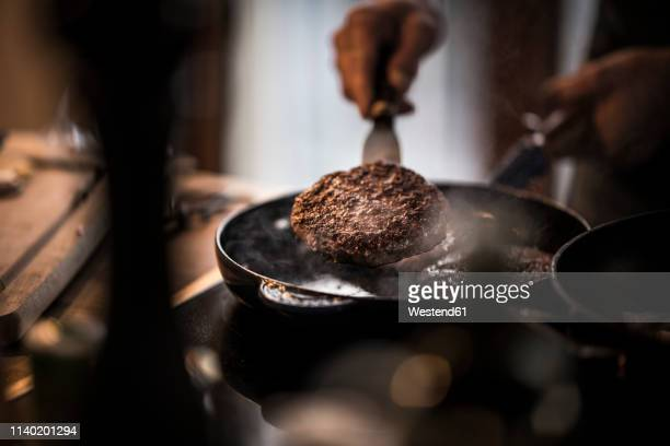 man frying beef patties in a pan - food state stock pictures, royalty-free photos & images