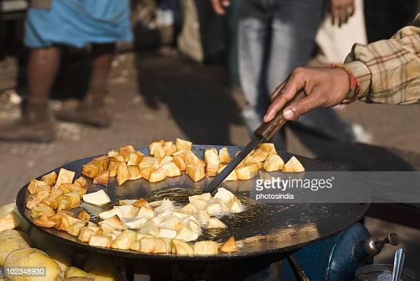 Man frying potato slices on a griddle, Delhi, India