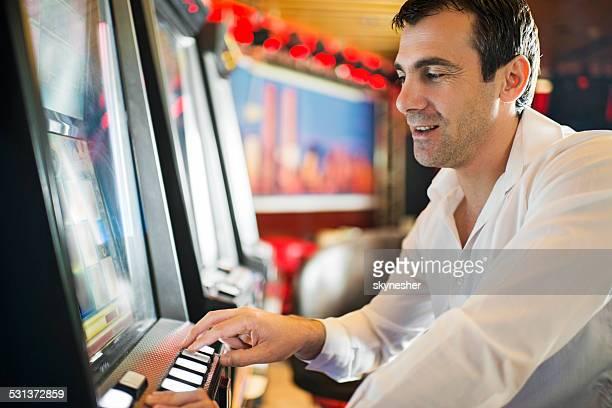 Mann Spielen am Spielautomaten.