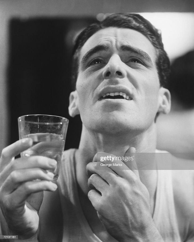 Man gargling, touching throat (B&W) : Stock Photo