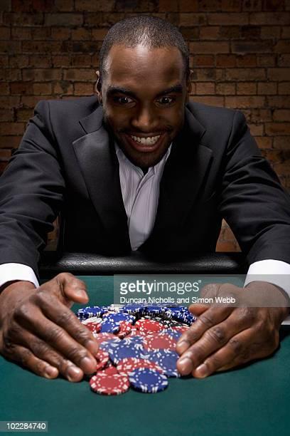 Man gathering poker chips in casino