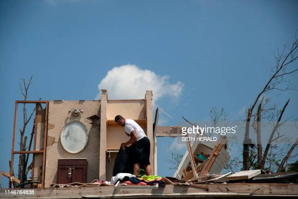 TOPSHOT A man gathers his belongings from his damaged home in Trotwood Ohio on May 28 after powerful tornadoes ripped through the US state overnight...