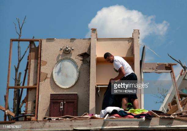 A man gathers his belongings from his damaged home in Trotwood Ohio on May 28 after powerful tornadoes ripped through the US state overnight causing...