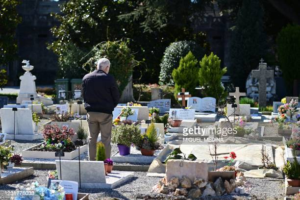 Man gathers his thoughts on March 15, 2021 in front of a grave of a relative who died from the coronavirus, at the Camp B1 in the Monumental cemetery...