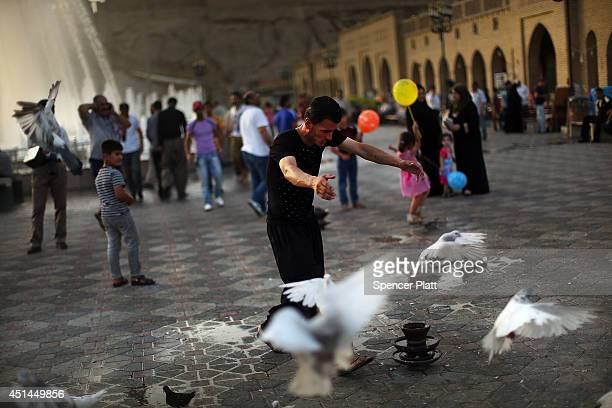 A man gathers pigeons near the Citadel in Erbil on June 29 2014 in Erbil Iraq Tens of thousands of displaced Iraqis and Syrians have converged on the...