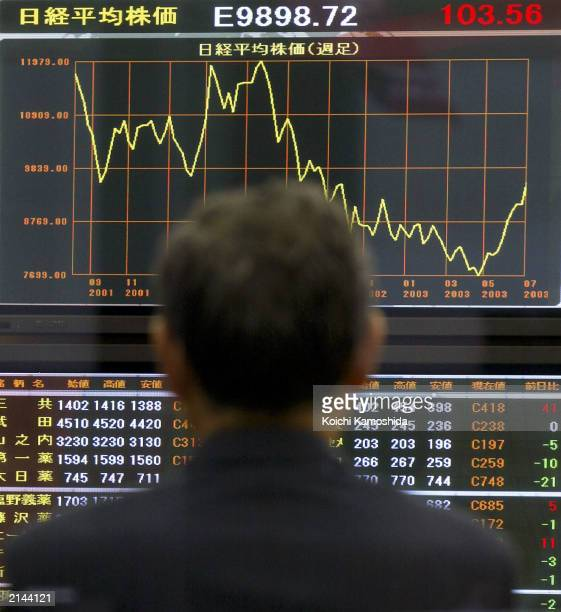 A man gazes at an electronic quotation board displaying the Nikkei Stock Average July 8 2003 in Tokyo Japan The Nikkei briefly rose above 10000 for...