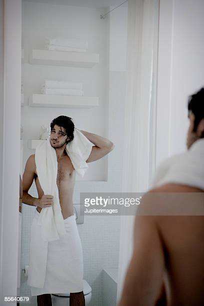 Man gazing at reflection in mirror while drying off with tow