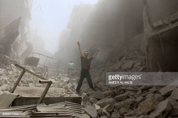 TOPSHOT A man gestures amid the rubble of destroyed buildings following a reported air strike on the rebelheld neighbourhood of alKalasa in the...