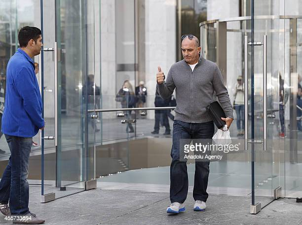 A man gestures as he exits the Apple store on Fifth Avenue after being one the first person purchasing the new iPhone 6 plus in New York United...
