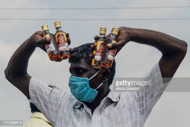 A man gestures as he shows bottles of alcohol bought from a liquor shop after the government eased a nationwide lockdown imposed as a preventive...
