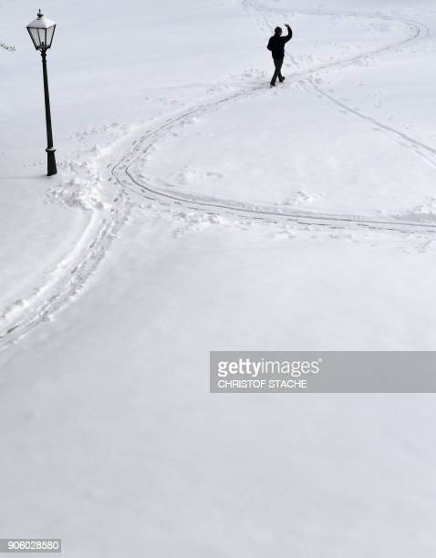 A man gestures as he walks through the snow on January 17 2018 in Irsee southern Germany / AFP PHOTO / CHRISTOF STACHE