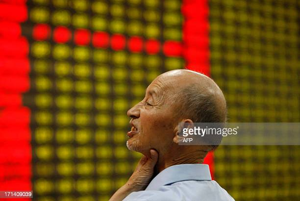 Man gestures as he watches stock activity at a stock exchange in Huaibei, north China's Anhui province on June 24, 2013. Chinese shares slumped 5.30...