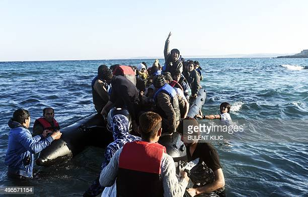 A man gestures as migrants and refugees board a dinghy to travel to the Greek island of Chios from Cesme in the Turkish province of Izmir on November...