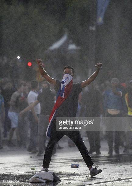 A man gestures as people clash with French riot policemen after attempting to enter the fan zone of the Champs de Mars next to the Eiffel tower in...