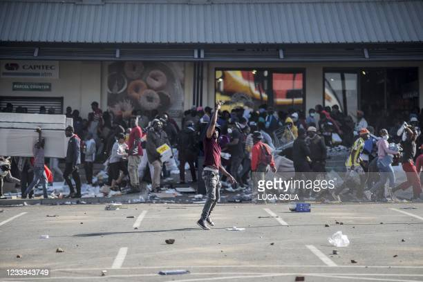 Man gestures as rioters loot the Jabulani Mall in the Soweto district of Johannesburg on July 12, 2021. - South Africa said it was deploying troops...