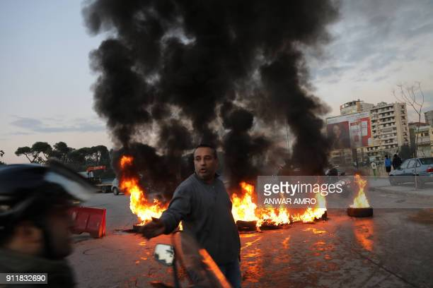 A man gestures as supporters of Lebanon's Shiite Muslim parliament speaker burn tyres to block a main road in Beirut on January 29 following a row...