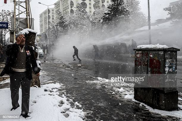 TOPSHOT A man gestures as Turkish police use a water cannon to disperse protestors on December 31 2015 in Diyarbakir during a demonstration after a...