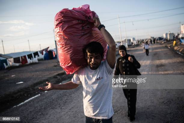 A man gestures at the camera as he carries a large bag on his shoulder in Khazir refugee camp on April 15 2017 near Mosul Iraq Khazir camp with a...