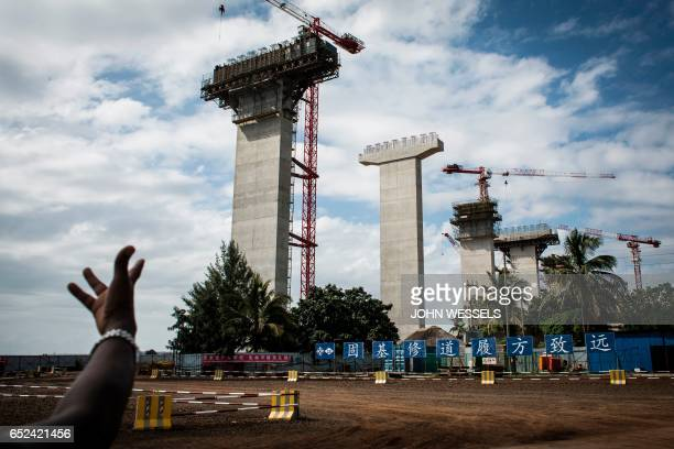 A man gestures at the Catembe side of the construction site of the MaputoCatembe Bridge which will be the longest suspension bridge in Africa once...