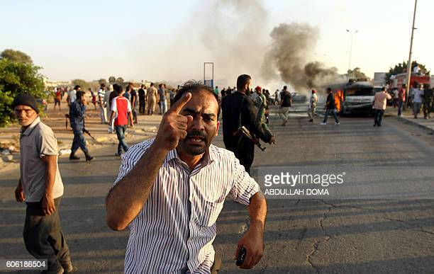 A man gestures at the site of a car bomb during a demonstration in support of General Khalifa Haftar in the coastal city of Benghazi on September 16...