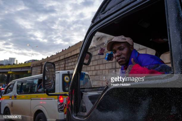A man gestures from a van as stranded commuters are forced to walk for hours to make their public transport connection on opposite sides of the city...