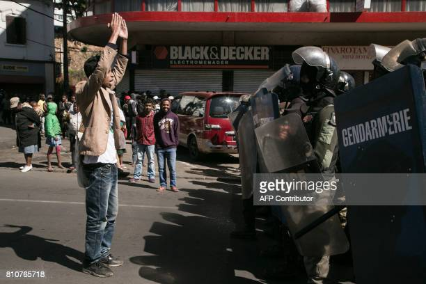 Man gestures in front of security forces as supporters of Madagascar's opposition party Tiako i Madagasikara take part in the party's 15th...