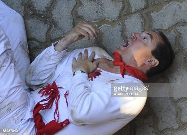 A man gestures in pain after been gored by a Miura fighting bull during the sixth run of the bulls of the San Fermin festival on July 12 in Pamplona...