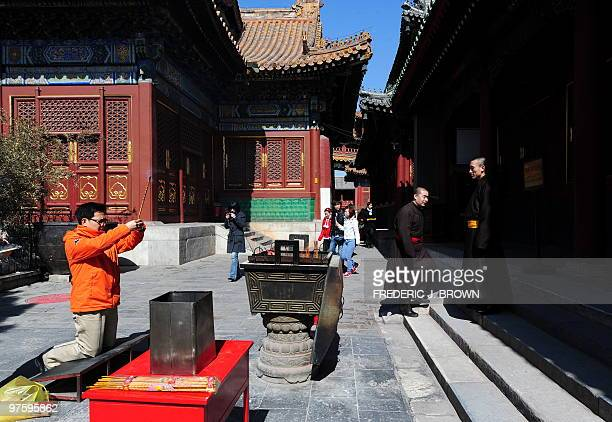 A man gestures in prayer while burning incense as a Tibetan Buddhist monk looks on at the Yonghegong also known as the Lama Temple a temple and...